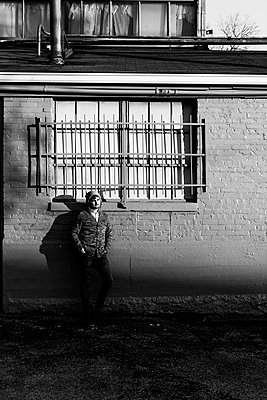 Young man at house wall - p1086m953572 by Carrie Marie Burr