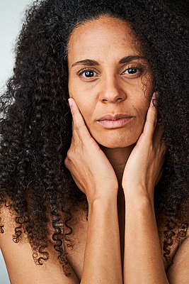 Serious curly haired woman touching face - p300m2264668 by Annika List