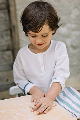 Cute boy playing with dough at backyard - p300m2281427 by Alberto Bogo