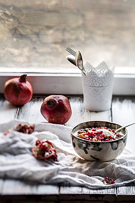 Healthy breakfast with pomegranate in yogurt, small vase with cutlery and pomegranates - p300m874025f by Susan Brooks-Dammann