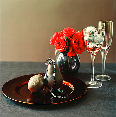 Tabletop with tableware glassware flower display and Christmas decorations - p349m695112 by Emma Lee