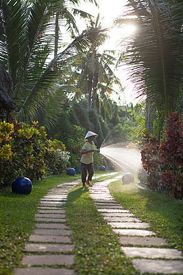 A hotel staff waters the garden at a small boutique resort on Phu Quoc island. Vietnam, Southeast Asia - p934m892929 by Matthew Dakin