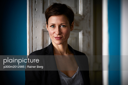 Portrait of a businesswoman leaning in door - p300m2012985 von Rainer Berg