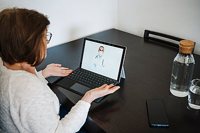Woman with laptop talking with doctor through video call at table in home - p300m2265665 by Eva Blanco