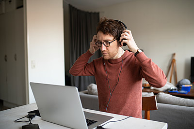 Man with headphones using laptop - p312m2139294 by Viktor Holm