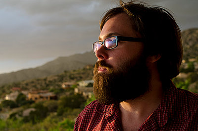 A man in his late twenties, takes in the view overlooking the city of Albuquerque, New Mexico. - p343m1011613f by Jeremy Wade Shockley