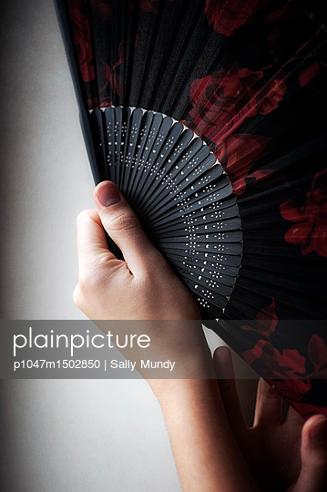 Close-up of womans hand holding a red and black fan - p1047m1502850 by Sally Mundy