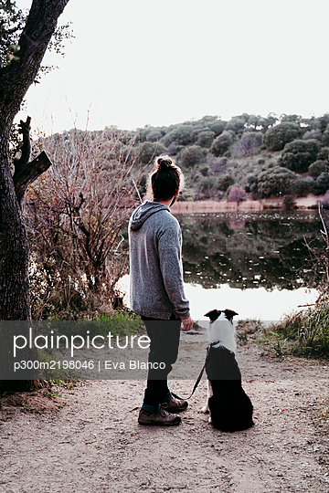 Man with his dog at lakeside - p300m2198046 by Eva Blanco