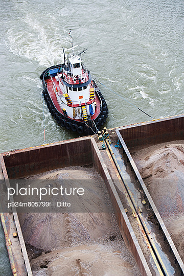 Tugboat pushing barges of sand, high angle view - p924m805799f by Ditto