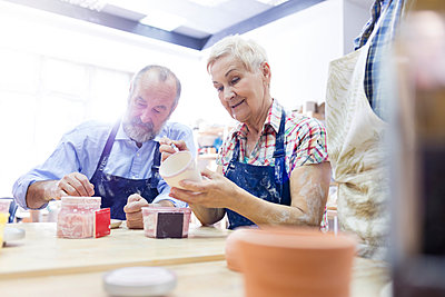Senior couple painting pottery in studio - p1023m1173717 by Agnieszka Olek