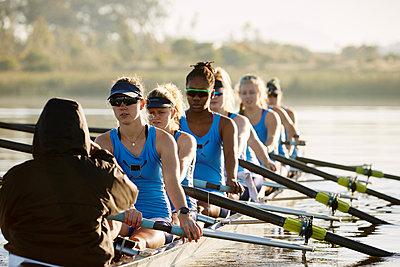 Female rowing team rowing scull on lake - p1023m1575818 by Richard Johnson