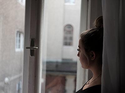 Junge Frau blickt aus dem Fenster - p1383m2057428 von Wolfgang Steiner
