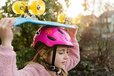 Girl carrying skateboard on head - p1427m2186309 by Jamie Grill