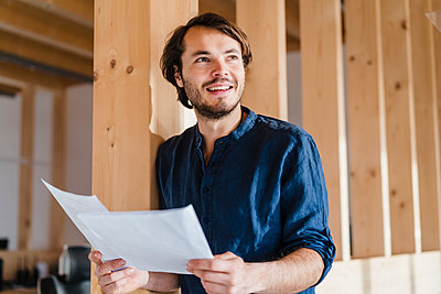 Smiling businessman holding documents in wooden open-plan office - p300m2170067 by Daniel Ingold