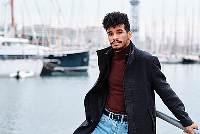 Young fashionable man wearing jacket while leaning on railing at harbor - p300m2250173 by Alvaro Gonzalez