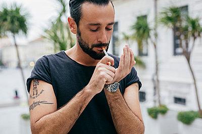 Mid adult man lighting cigarette - p429m1206787 by Mauro Grigollo