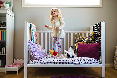 Girl jumping on day bed - p429m1418424 by Erin Lester
