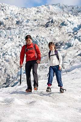 Mother and daughter walking on glacier - p429m727003f by Henn Photography