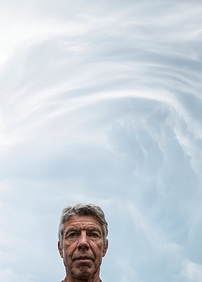 Storm clouds warning of tornadoes and hailstorms above the head of a senior man; Loveland, Colorado, United States of America - p442m1580390 by Debra Brash