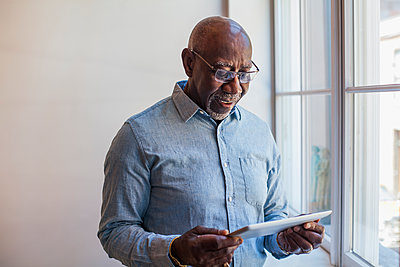Man using digital tablet near window - p555m1303740 by Strauss/Curtis