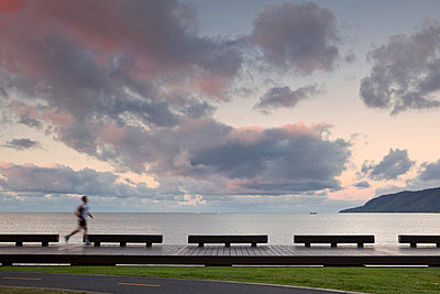 Jogger on the Esplanade boardwalk at dusk. - p6521895 by Andrew Watson