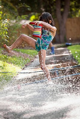 Girl holding welly, jumping over puddle of water on sidewalk - p924m1125659f by Kinzie Riehm