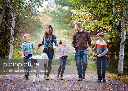 Happy family of five walking down country road with big dog. - p1166m2255660 by Cavan Images