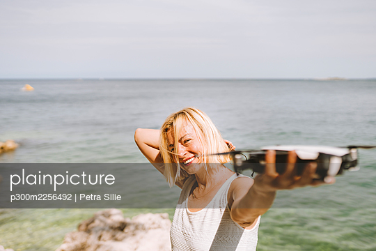 Smiling woman holding drone while standing against sea - p300m2256492 by Petra Silie