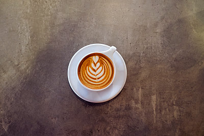 Overhead view of cappuccino on table at coffee shop - p1166m1144819 by Cavan Images