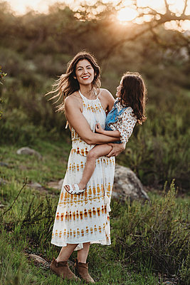 Full length view of mother and daughter embracing in sunny field - p1166m2131258 by Cavan Images