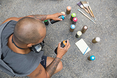 Overhead view graffiti artist with sketch pad and spray paint - p1192m1158150 by Hero Images