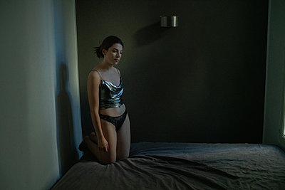 Young woman in lingerie kneels on the bed - p1321m2210593 by Gordon Spooner