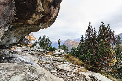 Hiker standing and looking over alpine plateau in autumn, Sondrio, Italy - p300m2144085 by 27exp