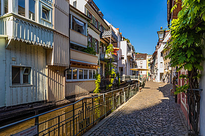 Germany, Baden-Wurttemberg, Freiburg im Breisgau, Stream flowing along cobblestone alley in old town - p300m2199034 by Werner Dieterich