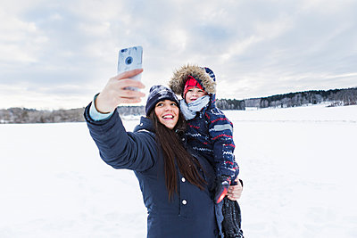 Mother taking selfie with son in snow - p352m1536600 by Calle Artmark