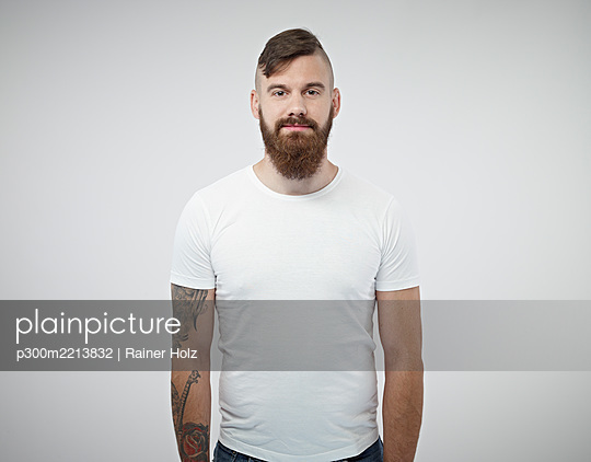 Portrait of smiling young man with shaved head, full beard and tattoo - p300m2213832 by Rainer Holz