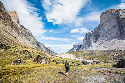 Backpacker hiking with portable solar panel attached to backpack. - p1166m2261214 by Cavan Images