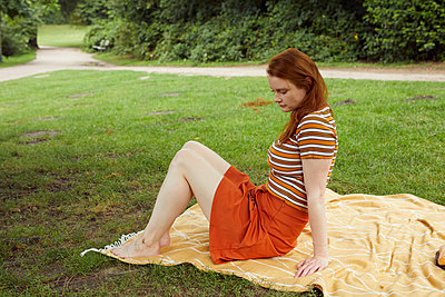 Red-haired woman sitting on picnic blanket - p1491m2176022 by Jessica Prautzsch