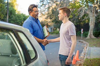 Learner driver and instructor shaking hands at car - p300m2013297 von zerocreatives