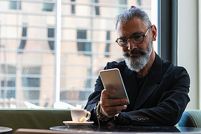 Businessman with eyeglasses using smartphone in coffee shop - p300m2276284 by NOVELLIMAGE