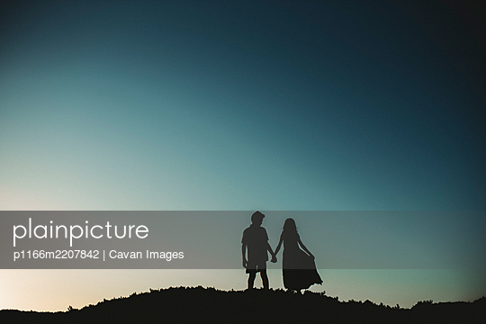 Silhouette of brother and sister standing on sand dune holding hands - p1166m2207842 by Cavan Images