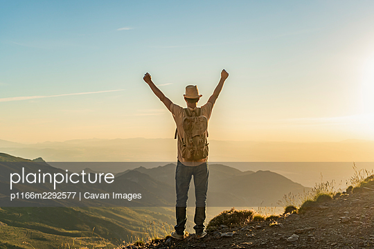 Back view of hiker man with backpack and raised hands at sunset - p1166m2292577 by Cavan Images
