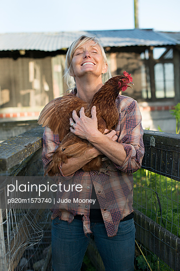 Woman holding rooster - p920m1573740 by Jude Mooney