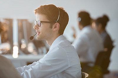 Businessman wearing headset in office - p1023m874343f by Tom Merton