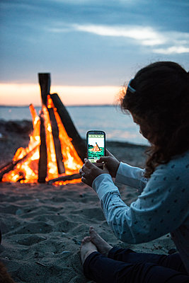 Woman taking photographs of campfire on beach - p1142m1362243 by Runar Lind