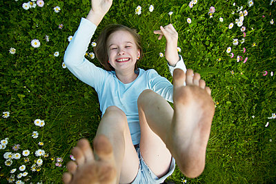 The girl lies on the grass with her arms and legs raised. - p1166m2290051 by Cavan Images