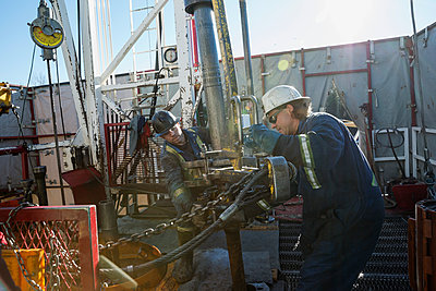 Male workers working drilling rig equipment gas plant - p1192m1127996f by Hero Images