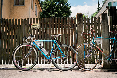 Racing bikes leaning against garden fence - p1437m2253428 by Achim Bunz