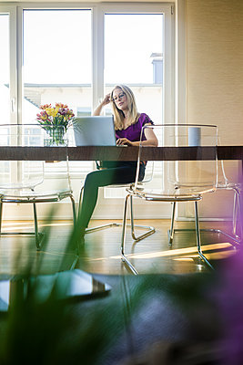 Businesswoman sitting at meeting table looking at laptop - p300m1588044 by Robijn Page