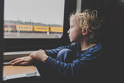 Little boy sitting in train looking out of window - p300m2160562 by Irina Heß
